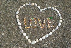 Heart from stones on the beach with the words Stock Photos