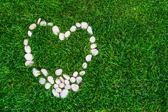 Heart of stones on green grass. Heart-shaped stones on grass stock photos
