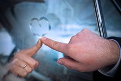 Heart on the stood glass. Newly-married couple draws Heart Shape at the frozen window of car Stock Photos