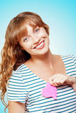 Heart Struck Woman In Romantic Love Affair. A beautiful woman holds a pink paper heart to her breast as she yearns for her sweetheart in a tender loving moment Stock Images