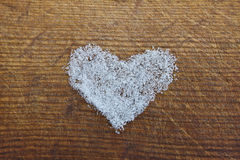 A heart of sugar on the wooden board. A heart of sugar on the wooden background Royalty Free Stock Photo