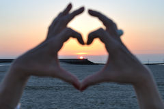 Heart of sunset. Two women hands join to form a heart filled with a sunset on a beach Royalty Free Stock Images