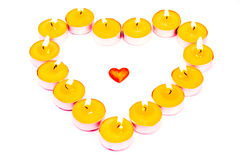 Heart surrounded with burning candles. Isolated on white Royalty Free Stock Image