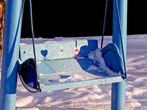 Heart on a swing. The small pink heart is covered with snow royalty free stock images