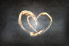 Heart symbol created by fire light. Over dark gray background stock photography