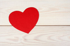 Heart symbol cut out of red paper. On a wood background Royalty Free Stock Image