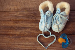 The heart symbol is drawn laces of children's shoes and a pacifier on the old wooden background. Stock Photos