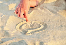 Heart symbol drawn in the sand. Finger girl drawing a heart in the sand Stock Image