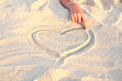 Heart symbol drawn in the sand 2. Heart symbol drawn in the sand. hand girl drawing a heart in the sand Stock Photography