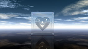 Heart symbol in glass cube under cloudy sky Stock Image