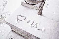 Heart symbol handwritten in snow on stone Royalty Free Stock Image