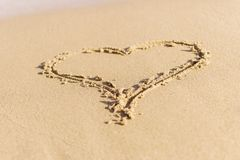 Heart the symbol of love drawn in the wet sea sand. The concept of love, honeymoon, Summer holiday stock images