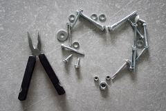 Heart symbol made of screws, nuts and bolts. Heart-shaped construction tools on concrete background. Love sign.  Royalty Free Stock Image