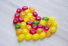 Heart symbol made of sweet candy. On white wooden background Stock Images