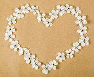 Heart symbol made of white spring flowers on brown paper background. Flat lay. Top view Royalty Free Stock Photos