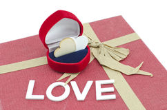 Heart symbol made from wood in red ring case on red gift box with ribbon made from recycle paper Royalty Free Stock Image