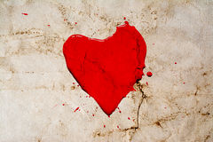 Heart symbol painted with red paint with splashes around on vintage background. Old retro style photo with cracks crumpled paper. Stock Photo