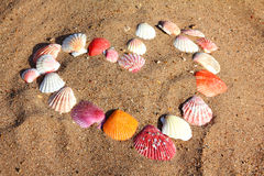 Heart symbol from shells on sand stock photography
