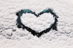 Heart symbol on snowy glass Stock Images
