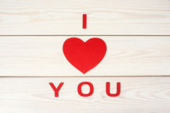 Heart symbol on a wood background with inscription I love you. Heart symbol cut out paper on a wood background with inscription I love you Stock Image