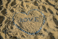 Heart symbol and word love on sand Stock Photo
