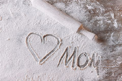 Heart symbol and word mom in flour on wooden table, Mothers day concept Royalty Free Stock Photo