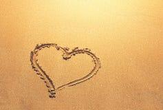 Heart symbol written on sandy beach. Background Stock Photo