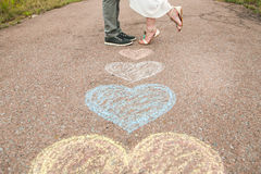 Heart symbols shaped with crayons on ground and two people in lo Stock Photo