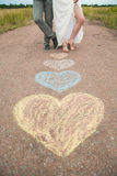 Heart symbols shaped with crayons on ground and two people in lo Royalty Free Stock Photos