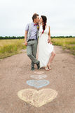 Heart symbols shaped with crayons on ground and two people in lo Royalty Free Stock Photography