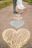 Heart symbols shaped with crayons on ground Stock Image