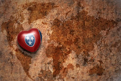 Heart with tennessee state flag  on a vintage world map crack paper background. Concept Stock Images