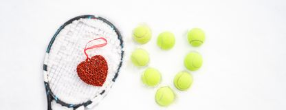 Heart of tennis balls and red heart on tennis racket on white snow winter background. Love Valentines day concept with tennis royalty free stock image