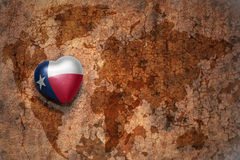 Heart with texas state flag on a vintage world map crack paper background. Concept royalty free stock image