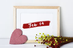 Heart and text feb 14 in a picture. A fabric heart, a wooden-framed picture with the text feb 14 and a bunch of red and yellow dry flowers on a white surface Royalty Free Stock Image