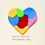 Heart and text world autism awareness day. The text world autism awareness day and a heart made from modelling clay of different colors on an off-white royalty free stock photography