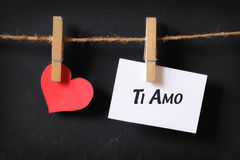 Heart with ti amo poster hanging. With blackboard background Royalty Free Stock Photos