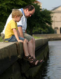 Heart to Heart. A father and son sitting on the edge of a pond Royalty Free Stock Images