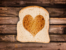 Heart toasted on a slice of bread,  on wooden planks Royalty Free Stock Image