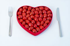 Heart with Tomatoes and cutlery. Dinner setting with heart filled with tomatoes for healthy living Royalty Free Stock Images