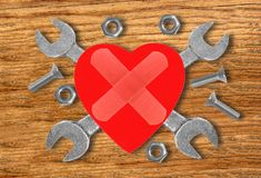Heart and tools. Concept: Renovation of heart over wooden Stock Photography