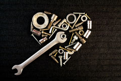 Heart of the tools and screw nuts. Heart of theart of the tools and screw nuts on a dark gray background Stock Image
