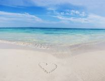 Heart on a tropical beach. Tropical beach and heart drawing on the sand Royalty Free Stock Image