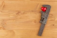 Heart under stress. Rusty vice crushed red heart. Working under stress. Royalty Free Stock Images