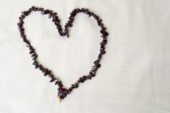 Heart for Valentine`s Day made of female beautiful beads, necklaces of brown dark stones, amber against a background of beige fab Stock Photography