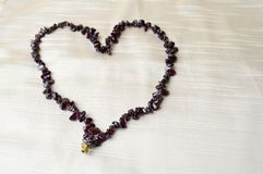 Heart for Valentine`s Day made of female beautiful beads, necklaces of brown dark stones, amber against a background of beige fab Stock Photos