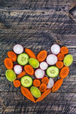 Heart vegetable early board wooden carrots cucumber leek Stock Photos