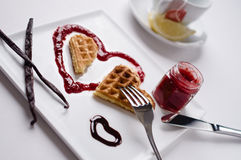 Heart waffle, marmalade, chocolate sauce, vanilla sticks, square. A heart shaped waffle on a heart shaped berry sauce and a chocolate sauce heart on a square Royalty Free Stock Photos