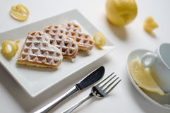 Heart waffles lemon zest, powdered sugar served on rectangular p. Heart shaped waffles with lemon zest, garnished with powedered sugar served on a rectangular Stock Photography