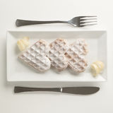 Heart waffles lemon zest, powdered sugar served on rectangular p. Heart shaped waffels with lemon zest, garnished with powedered sugar served on rectangular Royalty Free Stock Photo